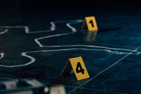 El enfoque selectivo del contorno de tiza y marcadores de evidencia en la escena del crimen Foto de archivo