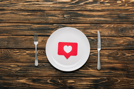 top view of white plate with red paper cut card with heart symbol near knife and fork on brown wooden surface Stock Photo