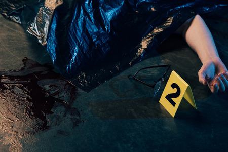 cropped view of covered corpse near glasses and evidence marker at crime scene Stock fotó