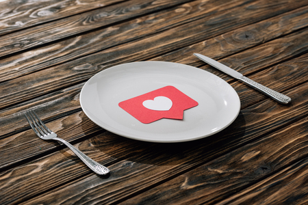 red paper cut card with heart symbol on white plate near knife and fork on brown wooden surface
