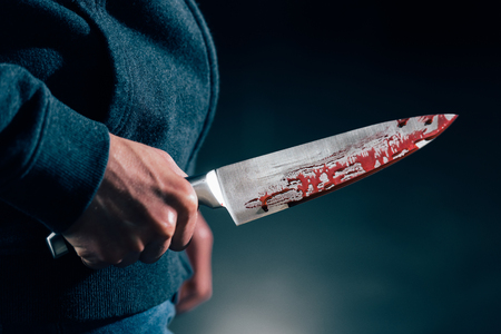 cropped view of murderer holding knife in blood 版權商用圖片