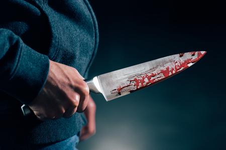 vue recadrée du meurtrier tenant un couteau dans le sang Banque d'images