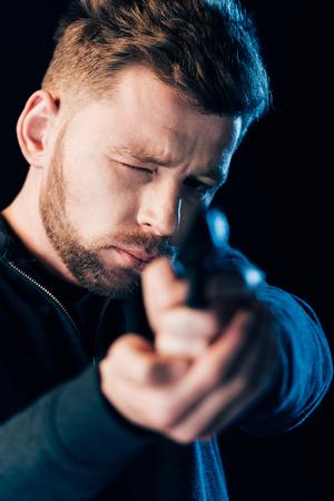 bearded criminal aiming gun at camera isolated on black