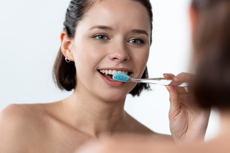 cheerful young woman brushing teeth in front of mirror