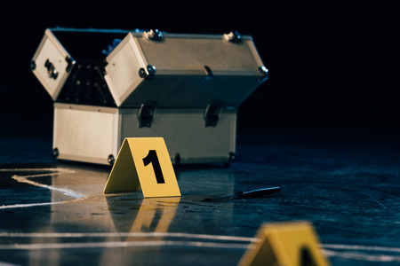 selective focus of knife, investigation kit, chalk outline and evidence markers at crime scene Reklamní fotografie