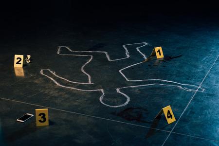 Contorno de tiza y marcadores de evidencia en la escena del crimen