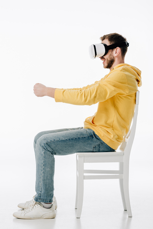 side view of young man in vr headset imitating driving while sitting on chair on white background Reklamní fotografie