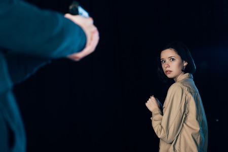 Ausgeschnittene Ansicht des Mörders, der eine Waffe auf eine Frau auf Schwarz zielt Standard-Bild