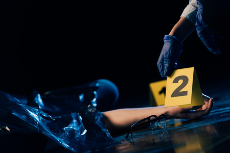 partial view of covered corpse and investigator with evidence marker at crime scene 스톡 콘텐츠 - 122958953