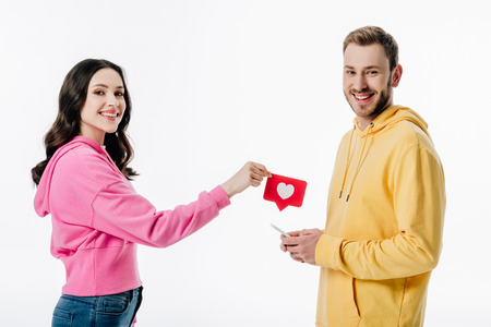 beautiful girl giving red paper cut card with heart symbol to smiling boyfriend with smartphone isolated on white 免版税图像