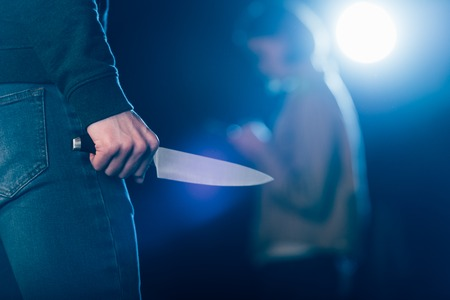 cropped view of killer holding knife near woman on black