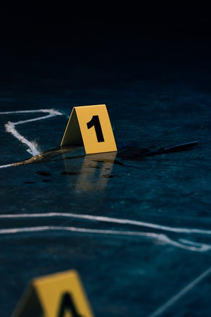 selective focus of chalk outline and evidence markers at crime scene