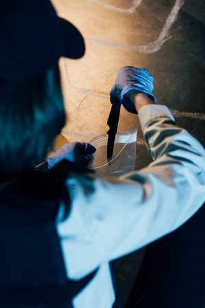 selective focus of investigator putting knife in zipper storage bags at crime scene Banque d'images