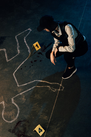 overhead view of investigator near chalk outline and evidence markers at crime scene