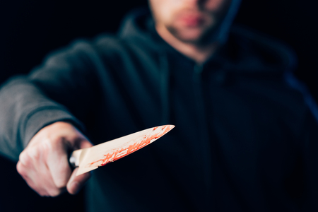 selective focus of killer holding knife isolated on black