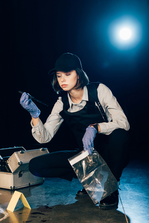 investigator holding knife and zipper storage bags at crime scene Stock Photo