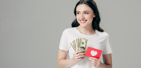 panoramic shot of happy girl holding dollar banknotes and red paper cut card with heart symbol isolated on grey