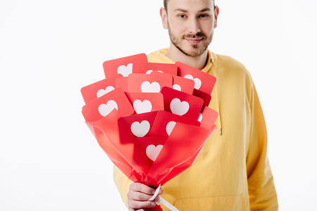 good-looking smiling man holding bouquet of red paper cut cards with hearts symbols and looking at camera isolated on white Reklamní fotografie