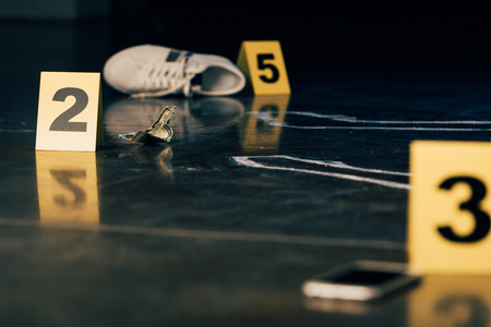 selective focus of smartphone, chalk outline, shoe, dollar banknote and evidence markers at crime scene 版權商用圖片