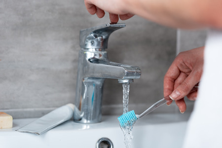 partial view of woman wetting toothbrush in sink