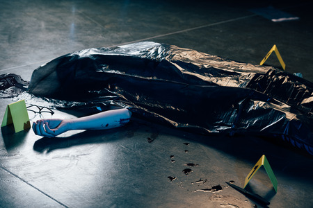 covered corpse with glasses on floor at crime scene Stock fotó - 122957020