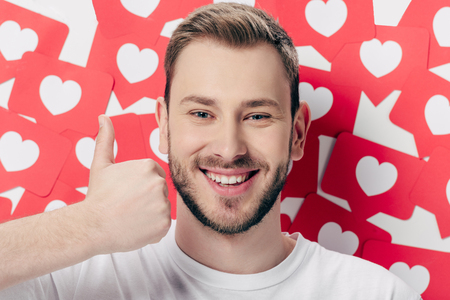 handsome cheerful man showing thumb up near red paper cut cards with hearts symbol and looking at camera