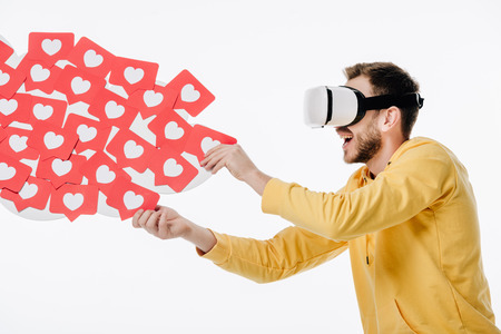 excited man using virtual reality headset while holding red paper cut cards with hearts symbols isolated on white 스톡 콘텐츠