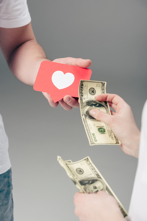 partial view of woman giving dollar banknotes to man with red paper cut card with heart symbol on grey background Stock Photo