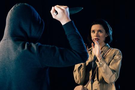 Vue partielle d'une femme attaquante criminelle avec un couteau isolé sur fond noir
