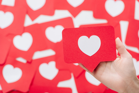 cropped view of female hand with red paper cut card with heart symbol