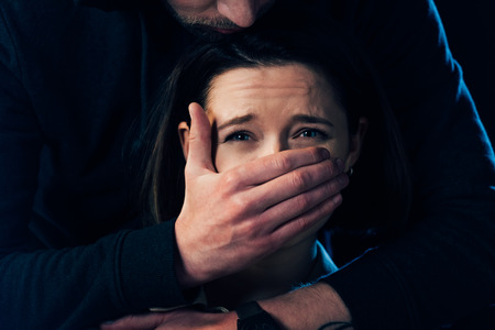 partial view of criminal attacking scared woman and covering her mouth isolated on black