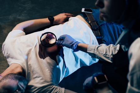 partial view of investigator using magnifying glass at crime scene Stock fotó