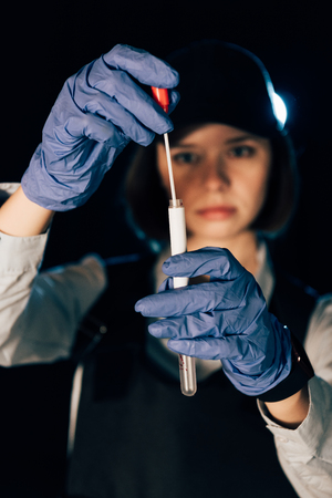 selective focus of investigator in rubber gloves holding swab and test tube at crime scene Stock Photo