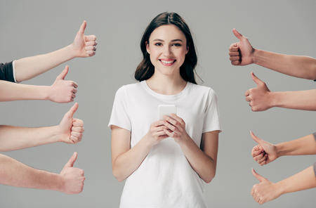 partial view of men and women showing thumbs up near cheerful girl with smartphone isolated on grey
