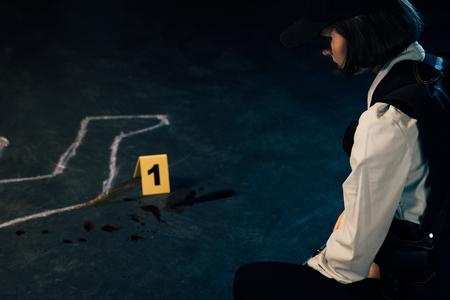 Vista recortada del investigador sentado cerca del contorno de tiza en la escena del crimen