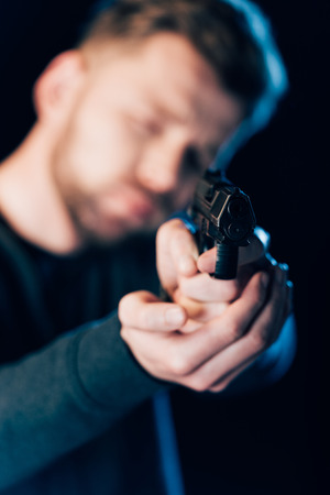 selective focus of criminal aiming gun at camera isolated on black 免版税图像