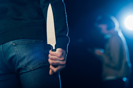 cropped view of murderer hiding knife behind back on black