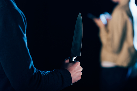 cropped view of killer holding knife near woman isolated on black 版權商用圖片