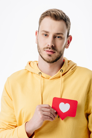 thoughtful young man holding red paper cut card with heart symbol and looking at camera isolated on white Stok Fotoğraf