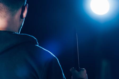 vue recadrée de tueur tenant un couteau sur fond noir