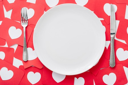 top view of empty white plate, knife and fork on red paper cut cards with hearts symbols