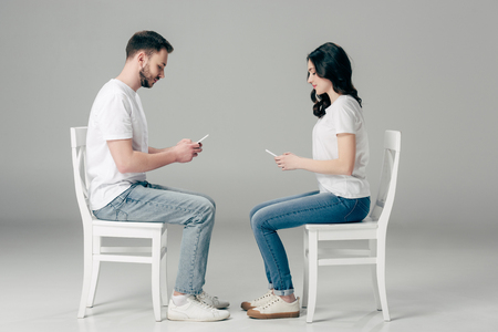 side view of concentrated man and woman in white t-shirts and blue jeans using smartphones while sitting on chairs on grey background