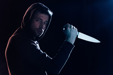 criminel dans des vêtements décontractés tenant un couteau et regardant la caméra sur fond noir Banque d'images