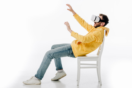 young man with outstretched hands sitting on chair in virtual reality headset on white background Stock Photo - 122956891