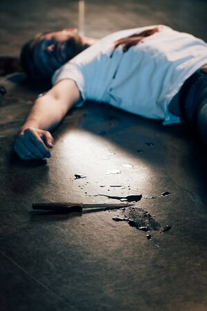 selective focus of dead man with blood on t-shirt on floor at crime scene