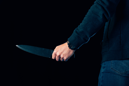 cropped view of killer holding knife isolated on black Imagens