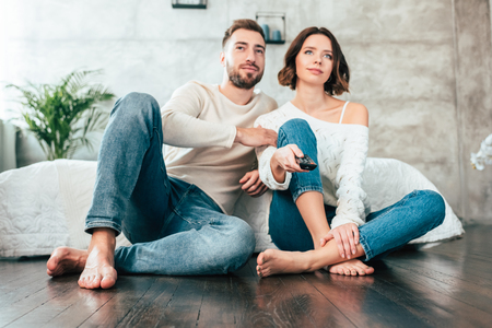 Low angle view of happy man sitting on floor near attractive woman with remote controller
