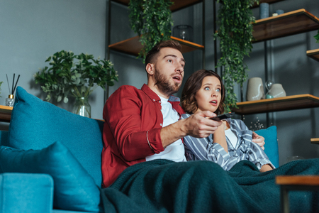Low angle view of shocked man holding remote controller while watching movie with woman at home 版權商用圖片