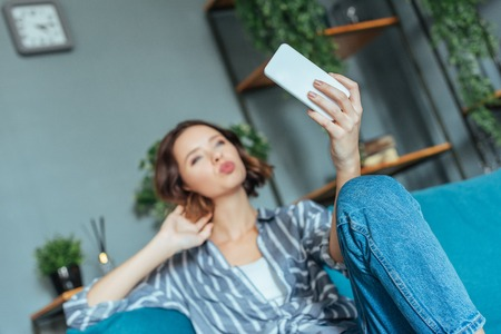 selective focus of woman with duck face taking selfie at home