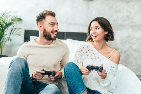 Happy man looking at cheerful woman holding joystick at home